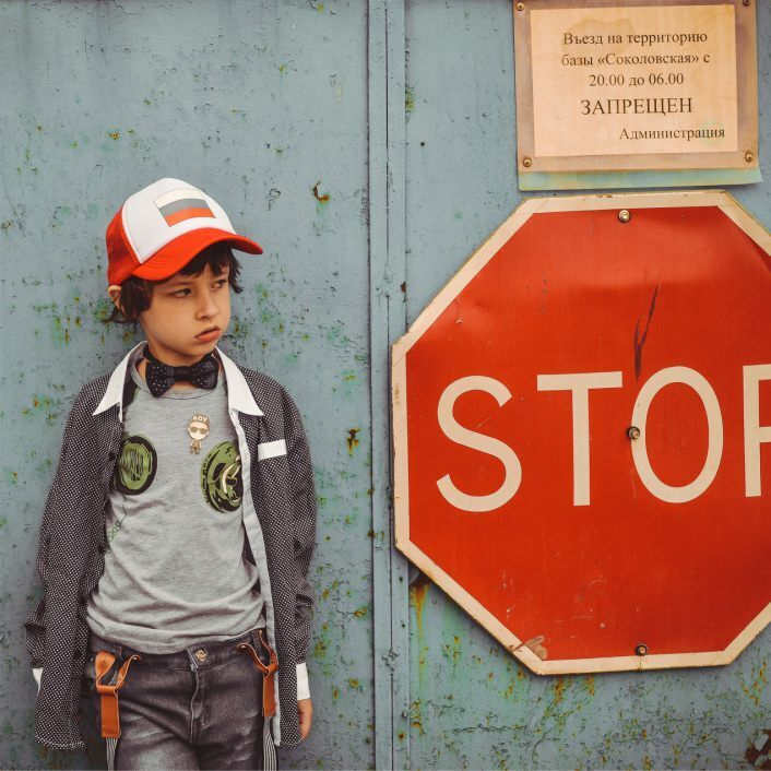 Young refugee boy standing beside a huge STOP sign.