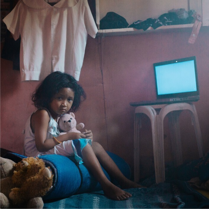 Child clutching a toy, sitting in a dark room with a computer screen in the background.