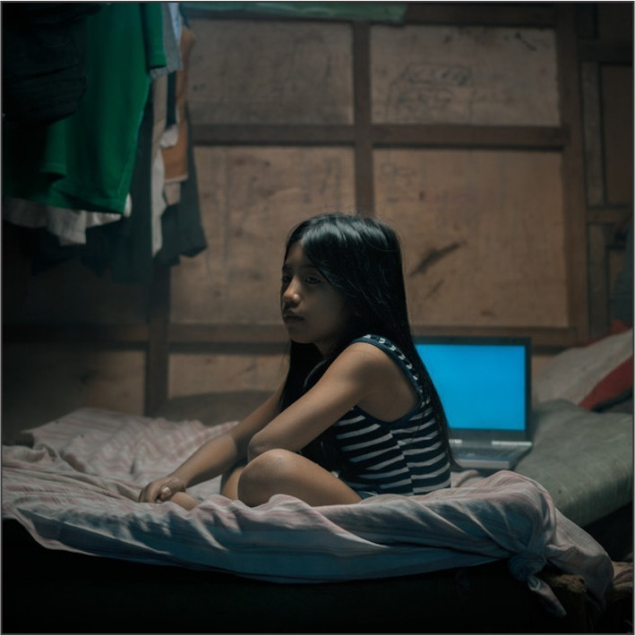 Filipino girl sitting on a mattress in a darkened room with a computer screen in the background.