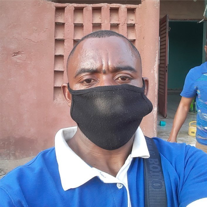 Congelese man wearing face mask outside a rustic building.