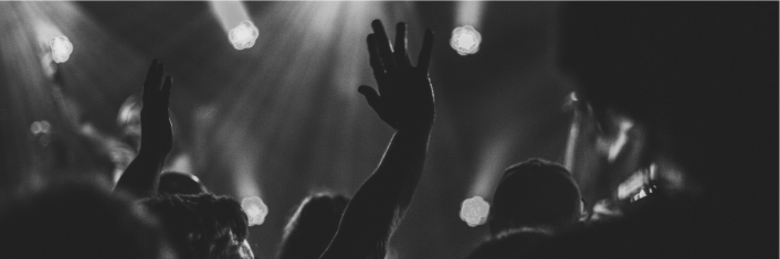 Black and white photo of hands raised in worship