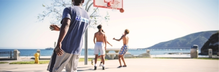 Three teens playing basketball outdoors
