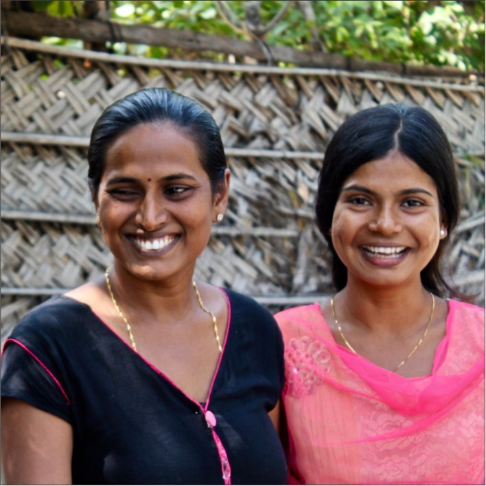 Two Sri Lankan women (one dressed in black; one dressed in coral) smiling.